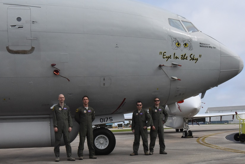 Photo shows four uniformed men standing in front of large aircraft.