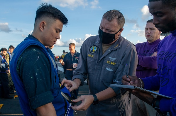 Chief Warrant Officer 4 Michael Neck, center, an inspector assigned to the Board of Inspection and Survey (INSURV), checks a CO2 cylinder on a life preserver on the flight deck of the Nimitz-class aircraft carrier USS Harry S. Truman (CVN 75).