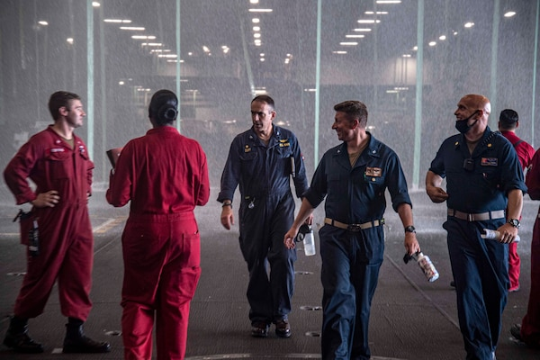 Capt. Gavin Duff, center, commanding officer of the Nimitz-class aircraft carrier USS Harry S. Truman (CVN 75), and Capt. Shane Marchesi, Truman's executive officer, speak with Sailors during an operational test of the aqueous film-forming foam sprinkler system in Truman's hangar bay.