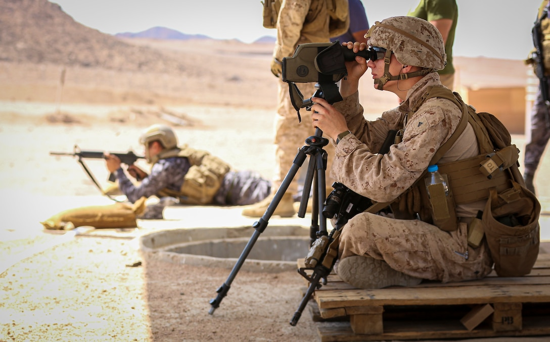 CAMP TITIN, Jordan (Sept. 21, 2021) U.S. Marine assigned to Fleet Anti-Terrorism Security Team acts as a spotter for a Jordanian Marine while participating in a gun shoot during Exercise Infinite Defender 21. Infinite Defender 21 is an annual, bilateral maritime infrastructure protection, explosive ordnance disposal, anti-terrorism force protection, and maritime security exercise between the Jordanian Armed Forces and U.S. Naval Forces Central Command, meant to enhance partnership and interoperability. (U.S. Marine Corps photo by Sgt. Benjamin McDonald)