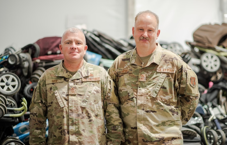 U.S. Air Force Chief Master Sgt. Marvin Boyd, Washington Air National Guard Command Chief, and Chief Master Sgt. Brandon Ives, 141st Air Refueling Wing command chief, pose for a photo in front of a large donation of strollers at Liberty Village, Joint Base McGuire-Dix-Lakehurst, New Jersey, Sept. 27, 2021. Boyd handed over the senior enlisted leader of Village Three position to Ives. The Department of Defense, through U.S. Northern Command, and in support of the Department of Homeland Security, is providing transportation, temporary housing, medical screening, and general support for at least 50,000 Afghan evacuees at suitable facilities, in permanent or temporary structures, as quickly as possible. This initiative provides Afghan personnel essential support at secure locations outside Afghanistan. (U.S. Air Force photo by Capt. Francine St Laurent)