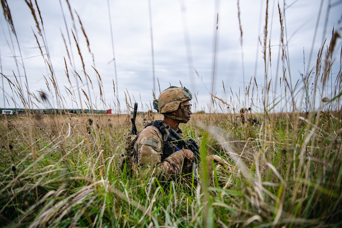 A paratrooper holding a weapon walks through a field of tall grass.