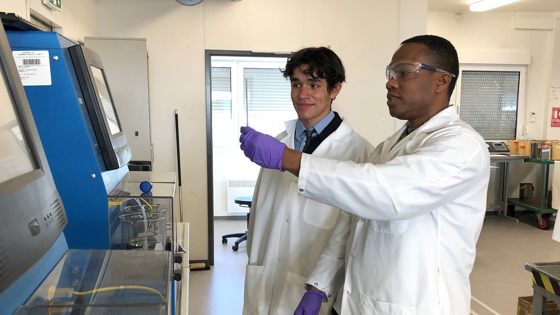 two people in lab coats using testing equipment