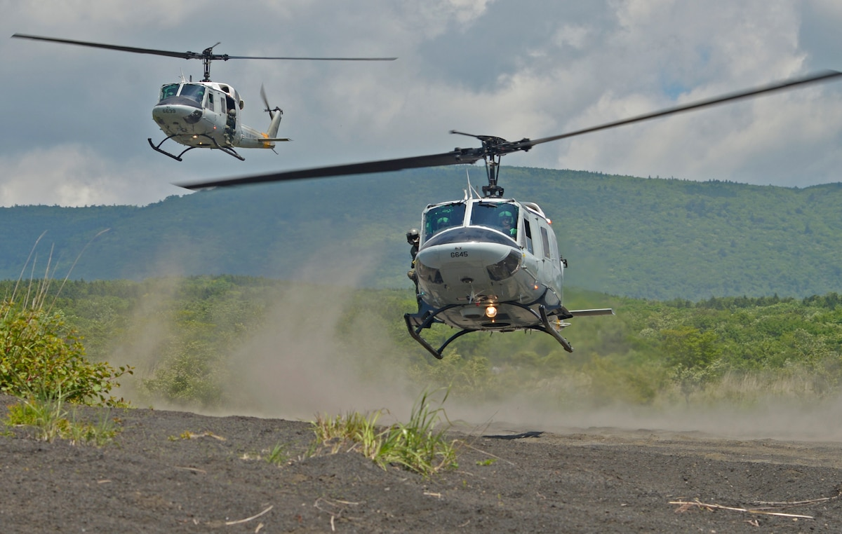 Two UH-1N Iroquois with the 459th Airlift Squadron take off from a drop zone near Mt. Fuji, Japan