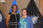 Two women stand in front of military flags