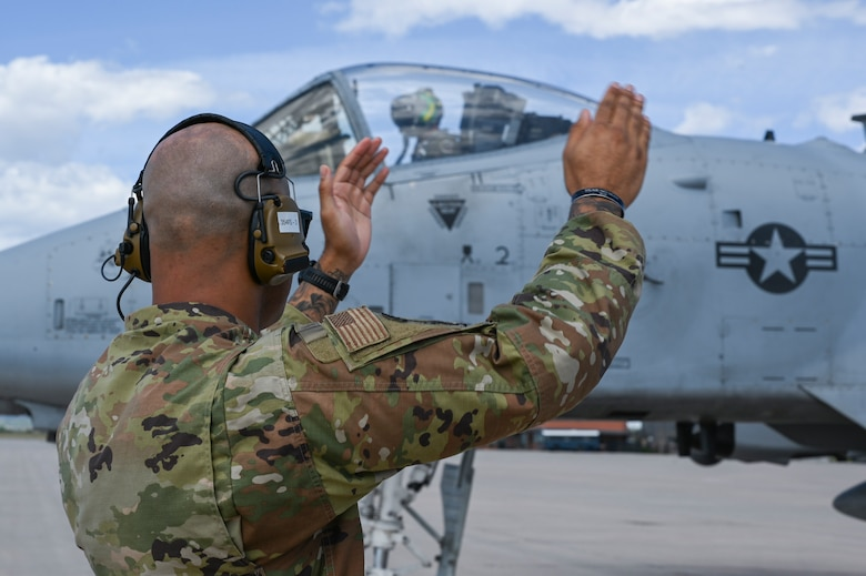 A photo of an Airman marshalling a jet