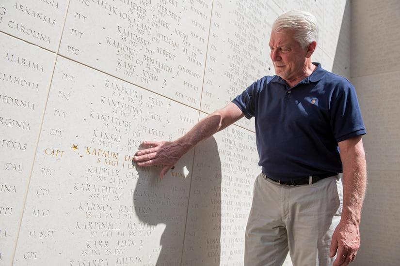 A man touches a memorial wall.