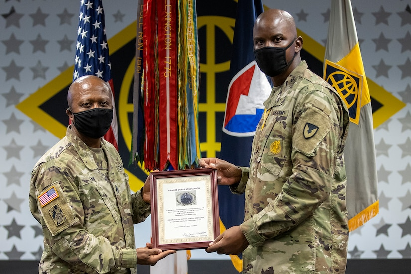 Command Sgt. Maj. Kenneth F. Law, U.S. Army Financial Management Command senior enlisted advisor, presents Sgt. Maj. Damien Russell, USAFMCOM Operations senior enlisted advisor, with the 837th Maj. Gen. Nathan Towson Medallion during a special ceremony at the Maj. Gen. Emmett J. Bean Federal Center in Indianapolis Aug. 26. The Towson Medallion was established by the Army Finance Corps Association on May 7, 1993, and is awarded in recognition of demonstrated exemplary contribution and service to the Army Finance Corps. (U.S. Army photo by Mark R. W. Orders-Woempner)