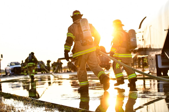 Firefighters carry a water hose.