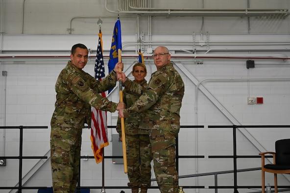 A man passes a blue flag to an older man.