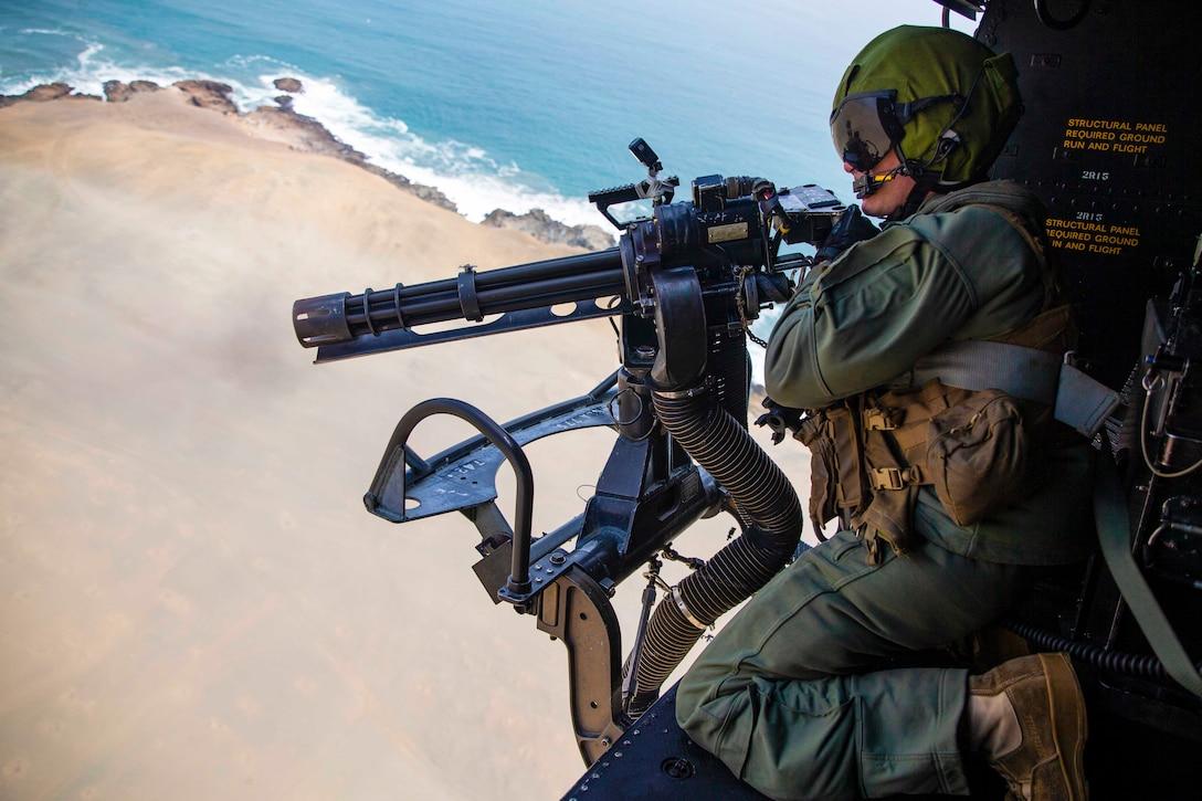 U.S. Marine Corps Sgt. Christophe J. Stump, an aerial observer with Special Purpose Marine Air-Ground Task Force - UNITAS, fires a GAU-17 minigun during UNITAS LXII in Lima, Peru, Sept. 28, 2021.