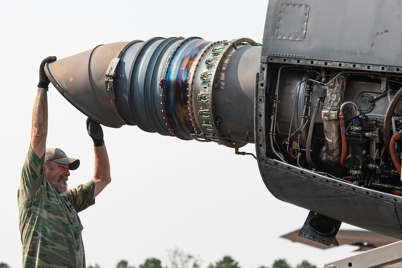 Photo of a contractor repositioning a C-130 Hercules engine.